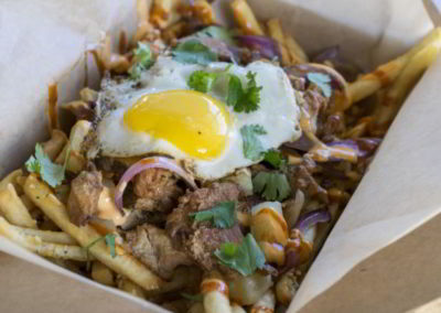 Fries in a box with meat onion parsley egg and dressing
