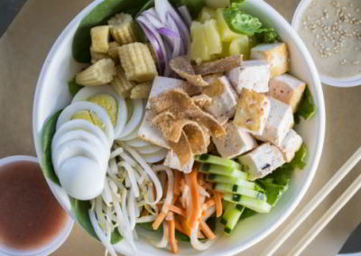 white bowl with tofu eggs corn onions bean sprouts carrots pineapple cucumber wonton strips with dressings on both sides